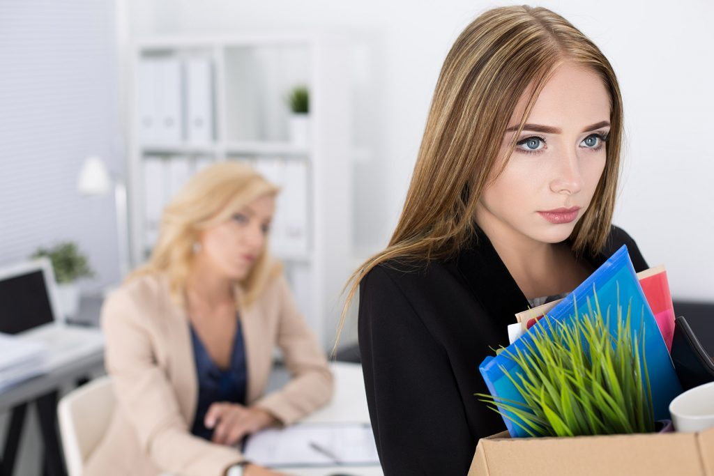 Young Woman Packing Up Her Stuff at the Office After Being Fired